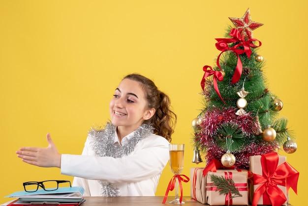 크리스마스 트리와 선물 상자와 노란색 배경에 악수 그녀의 테이블 뒤에 앉아 전면보기 여성 의사