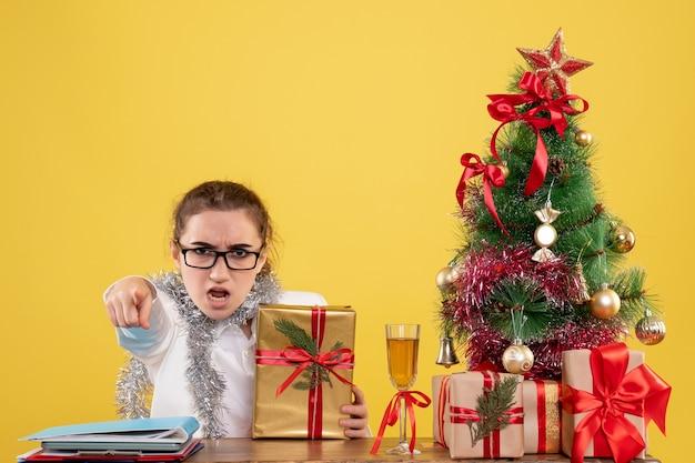 黄色の背景にクリスマスプレゼントと木と彼女のテーブルの後ろに座っている正面図の女性医師