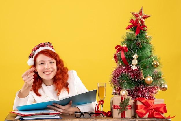 クリスマスツリーとギフトボックスと黄色の背景のドキュメントを読んでテーブルの後ろに座っている正面図の女性医師