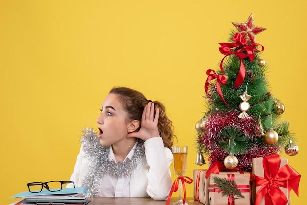 크리스마스 트리와 선물 상자와 노란색 배경에 듣고 테이블 뒤에 앉아 전면보기 여성 의사