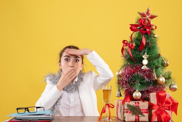 크리스마스 트리와 선물 상자와 노란색 배경에 테이블 뒤에 앉아 전면보기 여성 의사