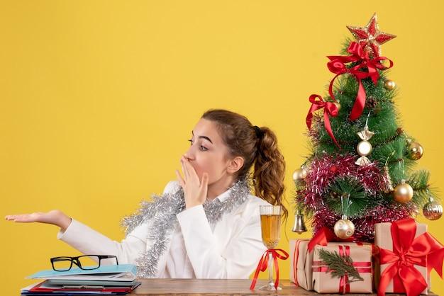 クリスマスツリーとギフトボックスと黄色の背景のテーブルの後ろに座っている正面図の女性医師