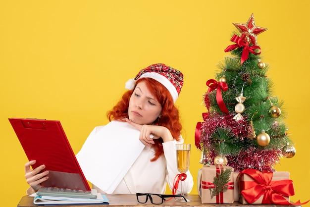 Вид спереди женщина-врач сидит за столом и читает анализ на желтом фоне с рождественской елкой и подарочными коробками