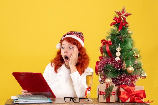 クリスマスツリーとギフトボックスと黄色の背景のノートを読んでテーブルの後ろに座っている正面図