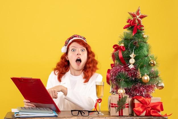 クリスマスツリーとギフトボックスと黄色の背景のノートを衝撃的に読んでテーブルの後ろに座っている正面図の女性医師
