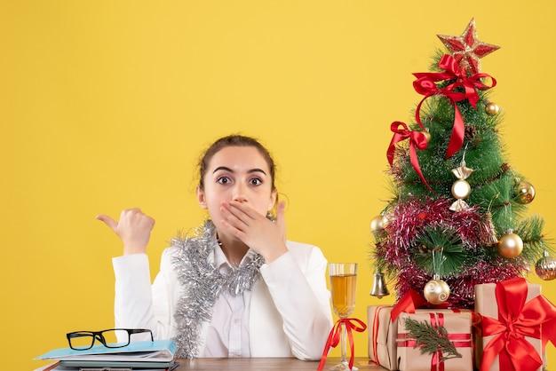 Вид спереди женщина-врач сидит за столом с рождественскими подарками и елкой на желтом фоне с рождественской елкой и подарочными коробками