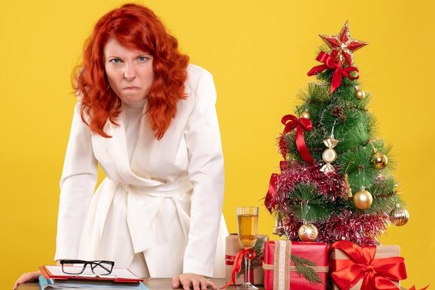 Вид спереди женщина-врач, сидящая за столом с рождественскими подарками, злая на желтом фоне с рождественской елкой и подарочными коробками
