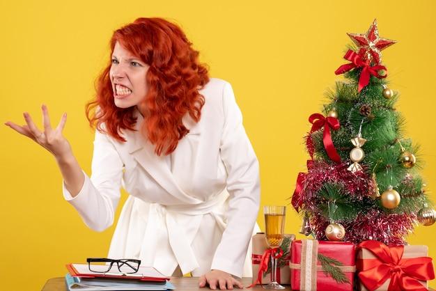 Вид спереди женщина-врач, сидящая за столом с рождественскими подарками, спорящая на желтом фоне с рождественской елкой и подарочными коробками
