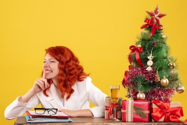 Вид спереди женщина-врач сидит за столом с рождественскими подарками и просит молчать на желтом фоне с елкой и подарочными коробками