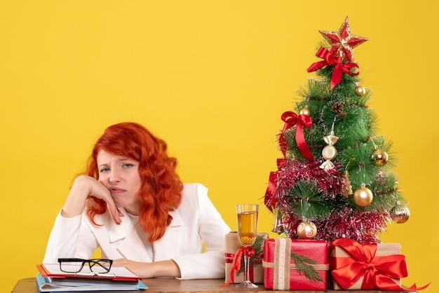 Вид спереди женщина-врач, сидящая за столом с рождественскими подарками, скучающая на желтом фоне с рождественской елкой и подарочными коробками