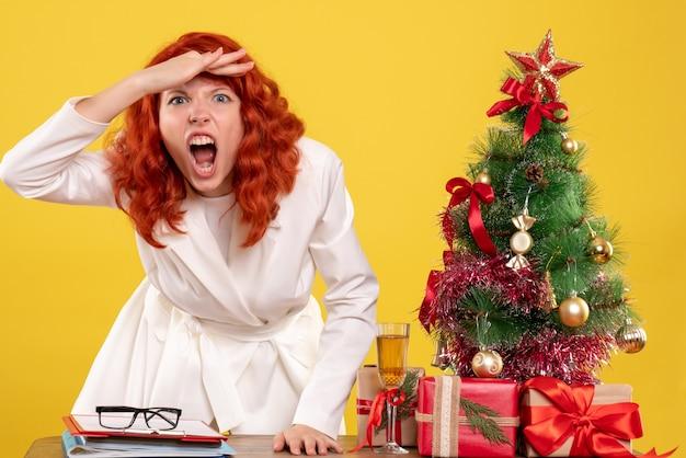 Вид спереди женщина-врач сидит за столом с рождественскими подарками и злится на желтом фоне