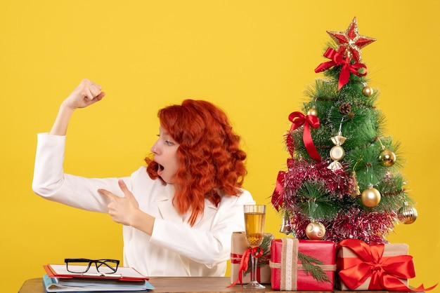 黄色の背景に曲がってクリスマスプレゼントとテーブルの後ろに座っている正面図の女性医師