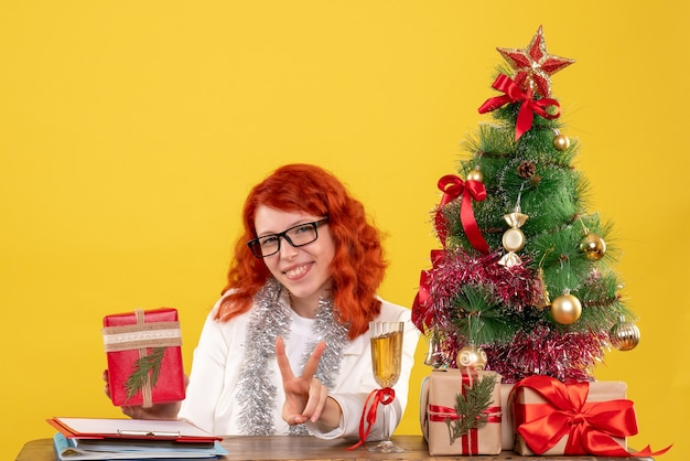 크리스마스 테이블 뒤에 앉아 전면보기 여성 의사 노란색 배경에 선물