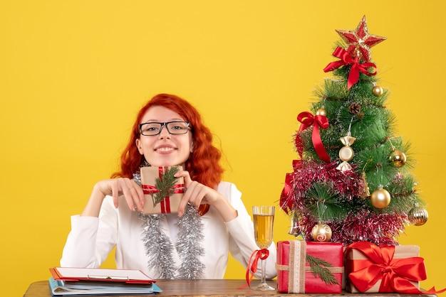 黄色の背景にクリスマスプレゼントとテーブルの後ろに座っている正面図の女性医師