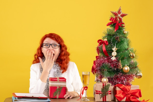 Вид спереди женщина-врач сидит за столом с рождественскими подарками на желтом столе