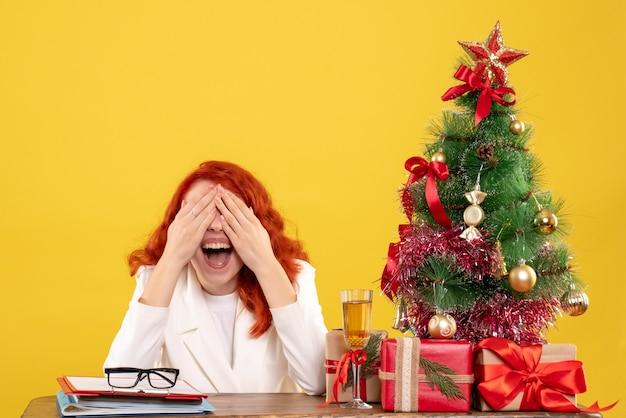 黄色い机の上にクリスマスプレゼントとテーブルの後ろに座っている正面図の女性医師