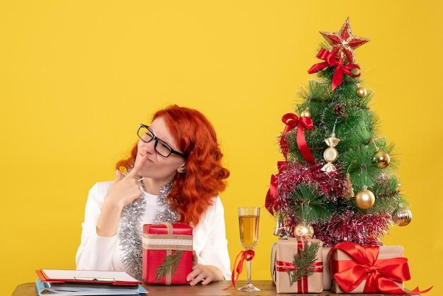 黄色のクリスマスプレゼントとテーブルの後ろに座っている正面図の女性医師