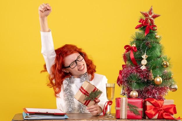 Вид спереди женщина-врач сидит за столом с рождественскими подарками и радуется на желтом фоне