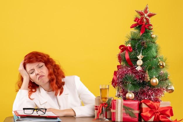 黄色の背景に疲れたクリスマスプレゼントとテーブルの後ろに座っている正面図の女性医師