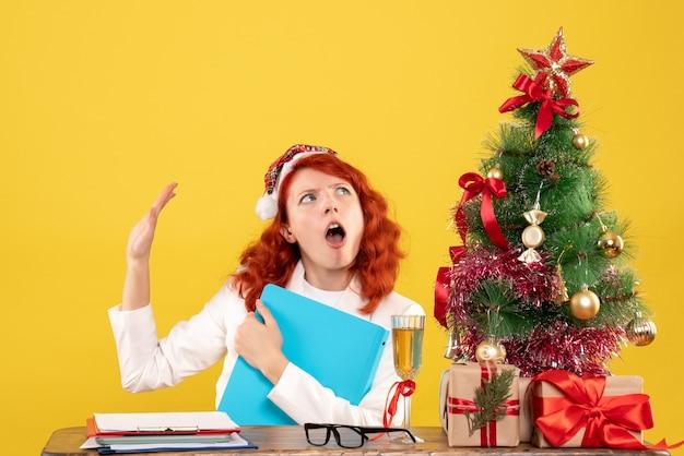 크리스마스 트리와 선물 상자와 노란색 배경에 그녀의 손에있는 문서와 테이블 뒤에 앉아 전면보기 여성 의사