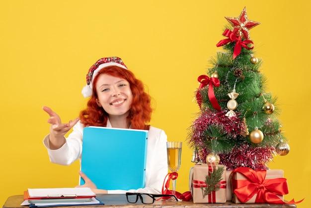 노란색 배경에 그녀의 손에있는 문서와 함께 테이블 뒤에 앉아 전면보기 여성 의사