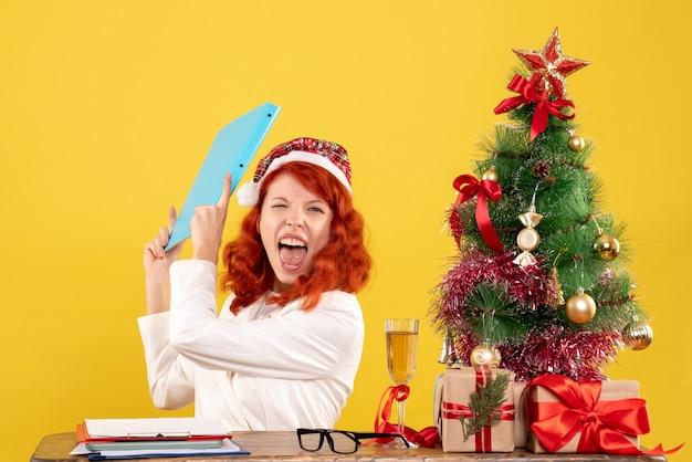 크리스마스 트리와 선물 상자와 노란색 책상에 그녀의 손에있는 문서와 테이블 뒤에 앉아 전면보기 여성 의사
