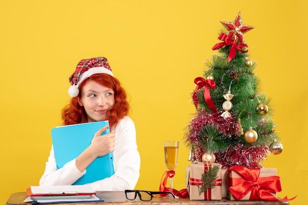 크리스마스 트리와 선물 상자 노란색에 그녀의 손에있는 문서와 함께 테이블 뒤에 앉아 전면보기 여성 의사