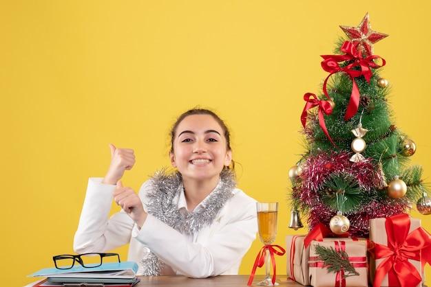 クリスマスプレゼントと黄色の背景の木とテーブルの後ろに座っている正面図の女性医師