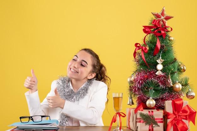 크리스마스 선물 테이블 뒤에 앉아 전면보기 여성 의사와 노란색 배경에 누군가에게 이야기하는 나무