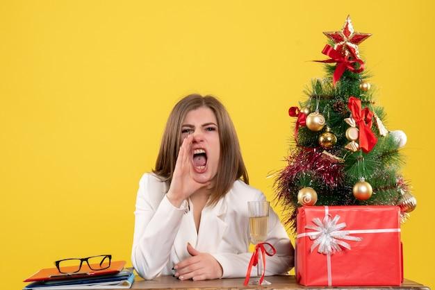 Medico femminile di vista frontale che si siede davanti al suo tavolo che chiama con rabbia su sfondo giallo con albero di natale e scatole regalo