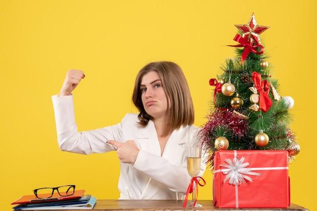 Medico femminile di vista frontale che si siede davanti al suo tavolo che flette su sfondo giallo con albero di natale e scatole regalo