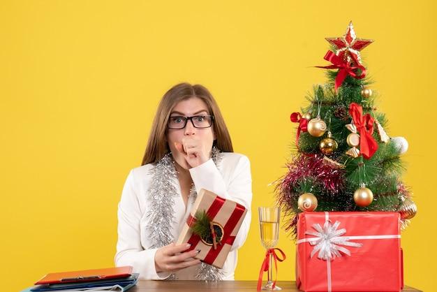 Medico femminile di vista frontale che si siede davanti al suo tavolo che tiene presente su sfondo giallo con albero di natale e scatole regalo