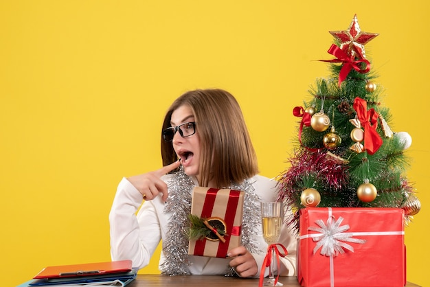 Front view female doctor sitting in front of her table holding present on yellow background with christmas tree and gift boxes