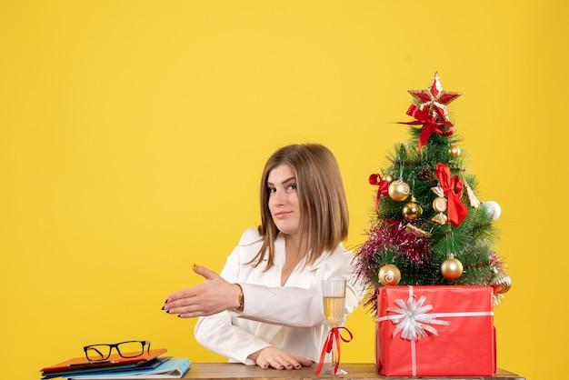 Medico femminile di vista frontale che si siede davanti al suo tavolo che agita le mani su fondo giallo con i contenitori di regalo e dell'albero di natale