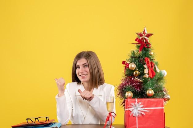 Medico femminile vista frontale seduto davanti al suo tavolo sorridente su sfondo giallo con albero di natale e scatole regalo