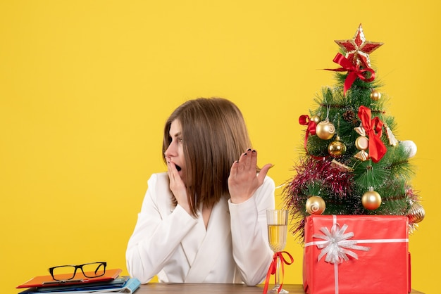 Front view female doctor sitting in front of her table on a yellow background with christmas tree and gift boxes
