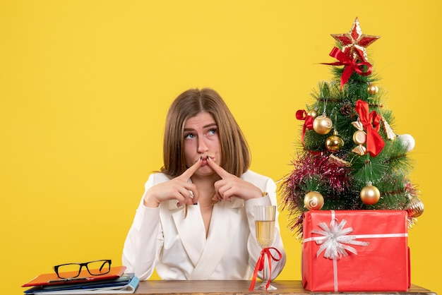 Front view female doctor sitting in front of her table on the yellow background with christmas tree and gift boxes