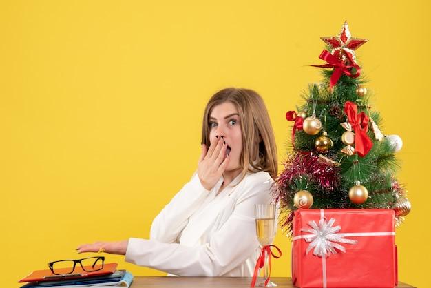 Medico femminile di vista frontale che si siede davanti al suo tavolo su sfondo giallo con albero di natale e scatole regalo