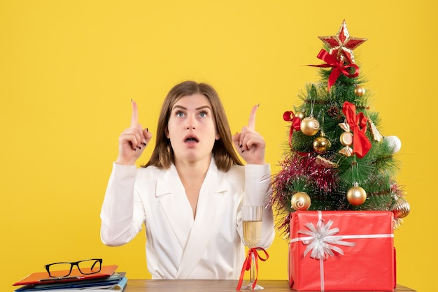 Front view female doctor sitting in front of her table on yellow background with christmas tree and gift boxes