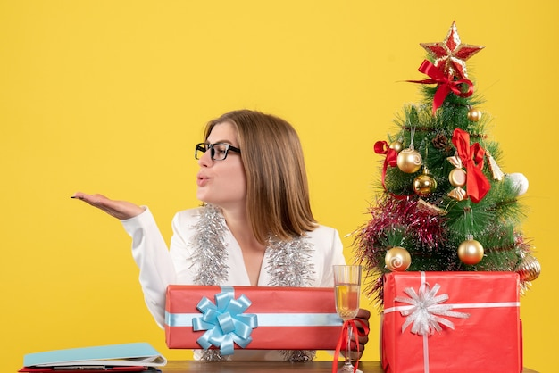 Front view female doctor sitting in front of table with presents and tree on a yellow background with christmas tree and gift boxes