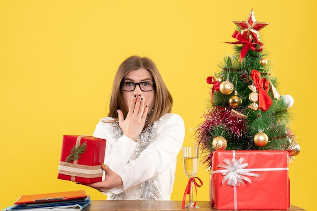 Front view female doctor sitting in front of table with presents and tree on a yellow background with christmas tree and gift boxes Free Photo