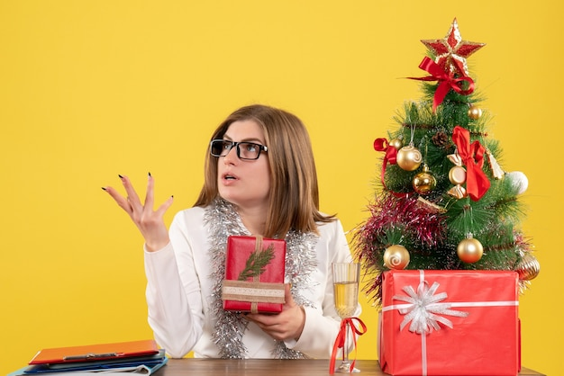 Front view female doctor sitting in front of table with presents and tree on the yellow background  with christmas tree and gift boxes