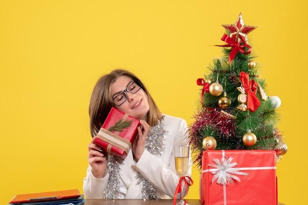 Medico femminile di vista frontale che si siede davanti al tavolo con regali e albero su sfondo giallo con albero di natale e scatole regalo