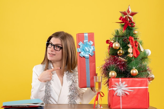Front view female doctor sitting in front of table with presents and tree on yellow background with christmas tree and gift boxes