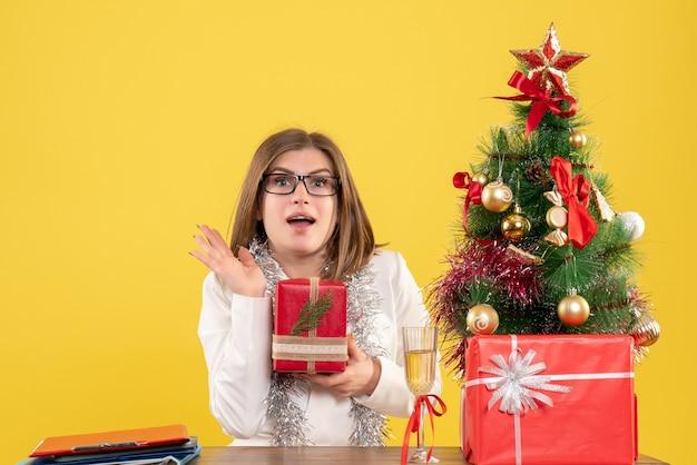 Medico femminile di vista frontale che si siede davanti al tavolo con regali e albero su sfondo giallo