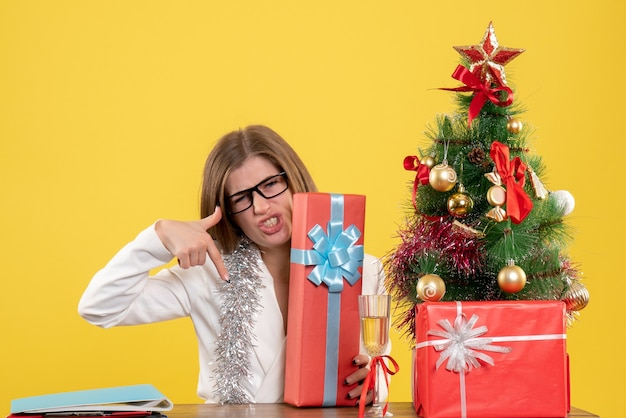 Front view female doctor sitting in front of table with presents and tree on the yellow background Free Photo
