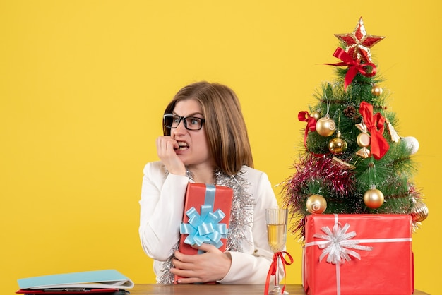 Front view female doctor sitting in front of table with presents and tree on yellow background