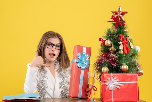 Front view female doctor sitting in front of table with presents and tree on yellow desk with christmas tree and gift boxes