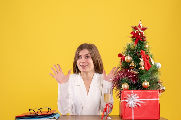 Front view female doctor sitting in front of table with xmas presents and tree on yellow background