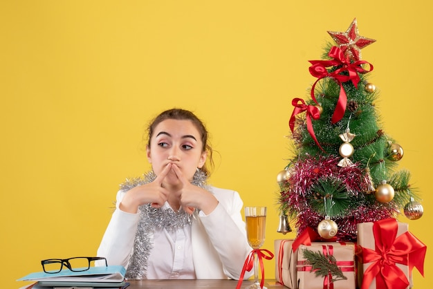 Front view female doctor sitting behind her table bored on yellow background with christmas tree and gift boxes